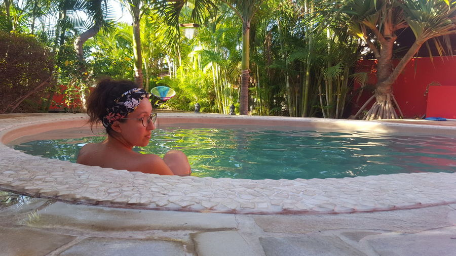 Rear view of woman sitting in hot tub against trees