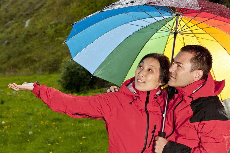 Happy friends with umbrella in rain