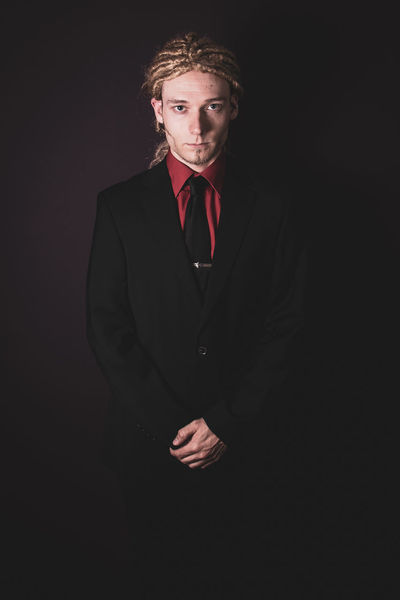 Adult Black Background Blond Hair Business Front View Hair Hairstyle Indoors  Looking At Camera Menswear One Person Portrait Serious Standing Studio Shot Suit Waist Up Well-dressed Young Adult Young Men