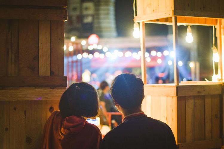 Rear view of couple at illuminated market