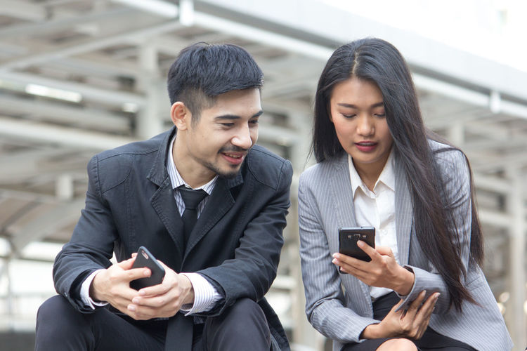 Businesswoman with colleague using phone
