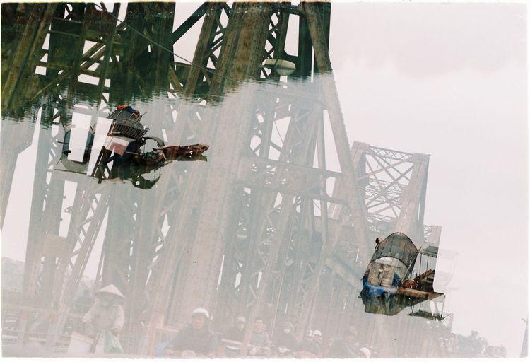Double exposure of metallic bridge and boats