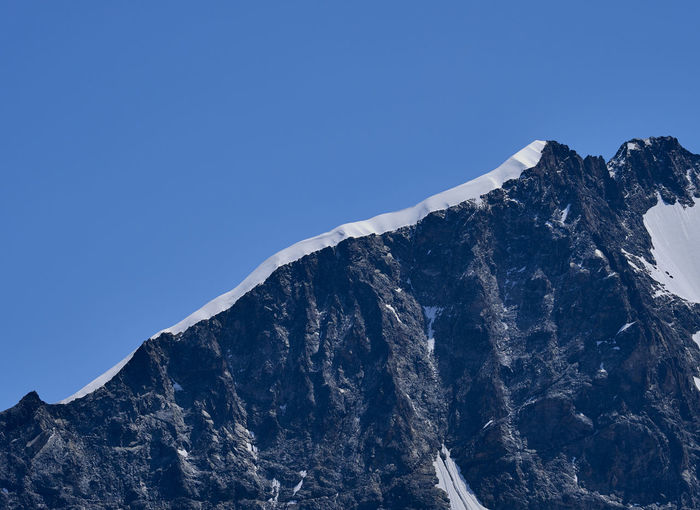 Low angle view of snowcapped mountains ridge against clear blue sky
