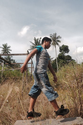Full length of boy on field against sky