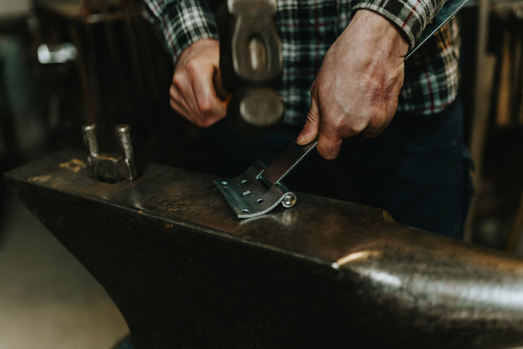 Midsection of blacksmith working on table in workshop