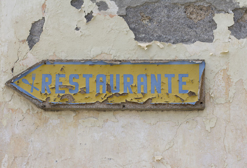 Restaurant sign in portuguese language Arrow City Funchal Letters Madeira Portugal Spanish Language Word Close-up Day Direction Information Island No People Old Outdoors Portuguese Language Restaurant Sign Text Wall - Building Feature Yellow