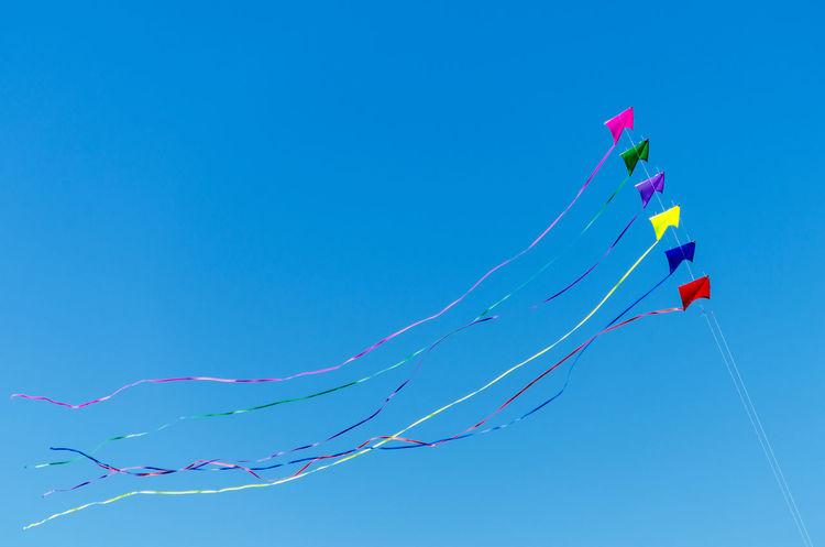 Rainbow colored kites flying against a beautiful blue sky Beach Beauty Coast Coastal Fly Flying Fun Kite Kites Landscape Lincoln City Lincoln City Beach Lincoln City, Oregon Oregon Oregon Coast Outdoor Outdoors Rainbow Sand Sea Summer Sunlight Texture Textured  Water