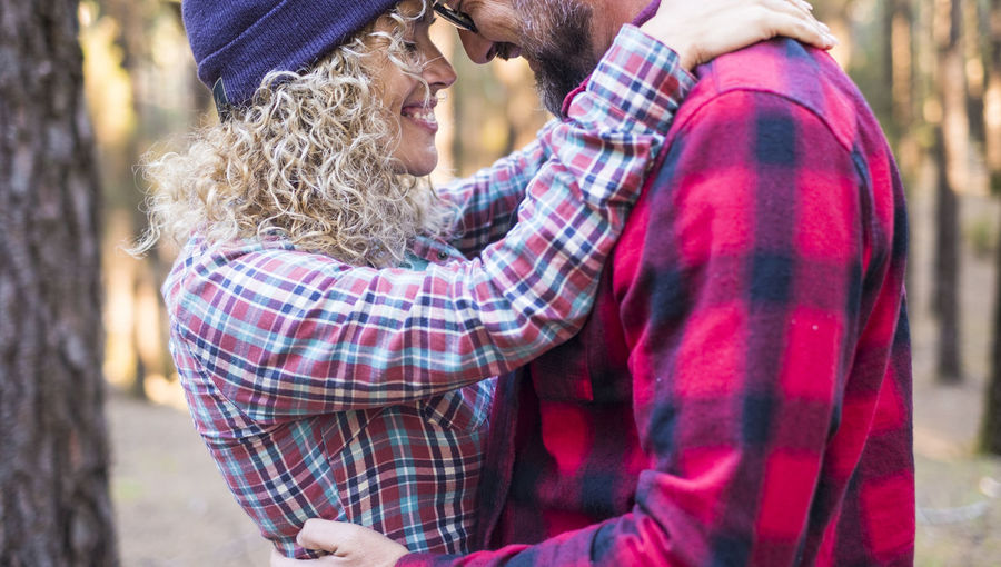 Midsection of couple standing on tree