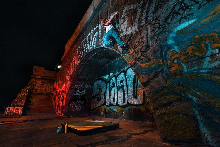 Low angle view of graffiti on wall at night