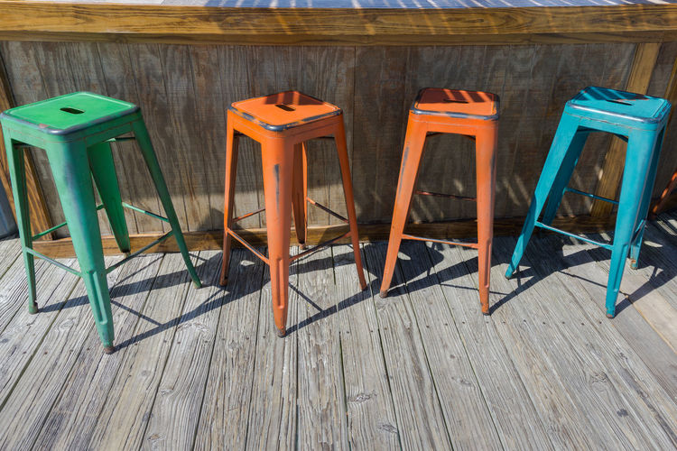 Colorful metal stools Isolated Pier Sit Bar Belly Up Chair Colorful Colorfull Deck Empty Furniture Furnitures In A Row Metal Multiple No People Outside Restaurant Saloon Seat Stool Stools Summer Vintage