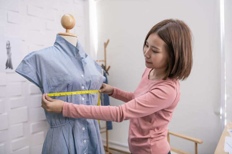Young woman measuring mannequin while standing against wall in fashion studio