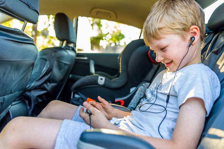 Side view of boy listening music while using mobile phone in car