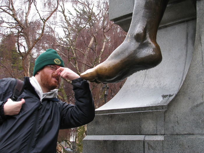 Man holding nose by wet foot statue
