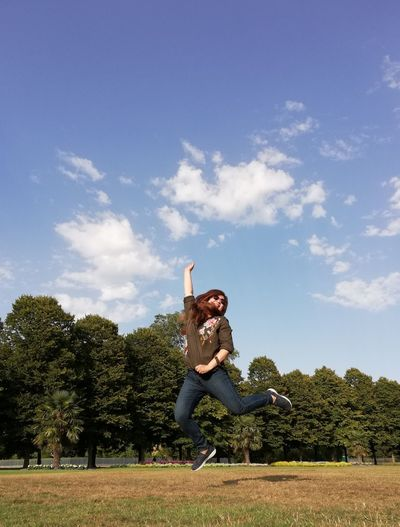 Happy Mature Woman With Arms Raised Jumping On Field Against Sky