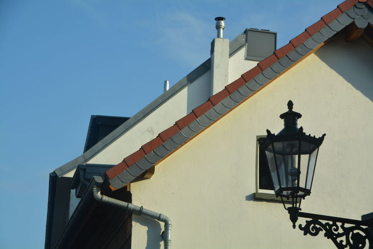 Low angle view of gas light and building against sky