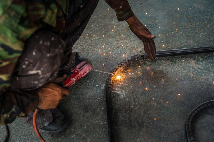 Low angle view of welder welding in workshop