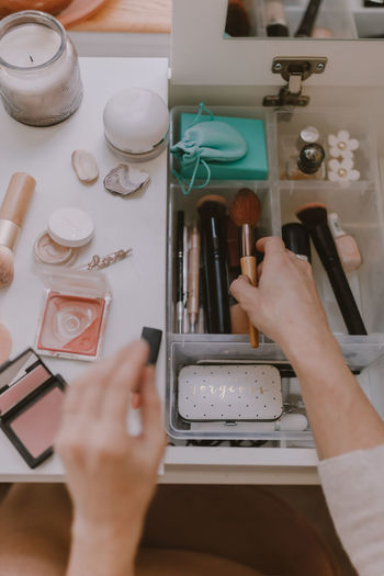 Cropped hands of woman holding beauty products on table at home