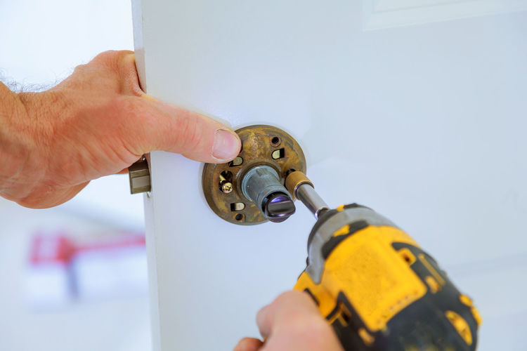 Cropped Hands Of Man Repairing Doorknob With Power Drill At Home