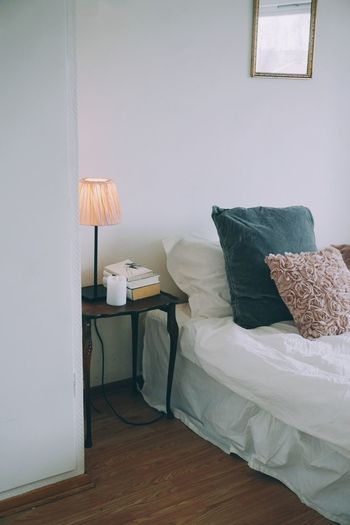 Electric lamp on bed against wall at home