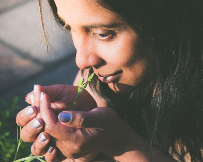 Close-Up Of Woman Smelling Plant Growing On Field