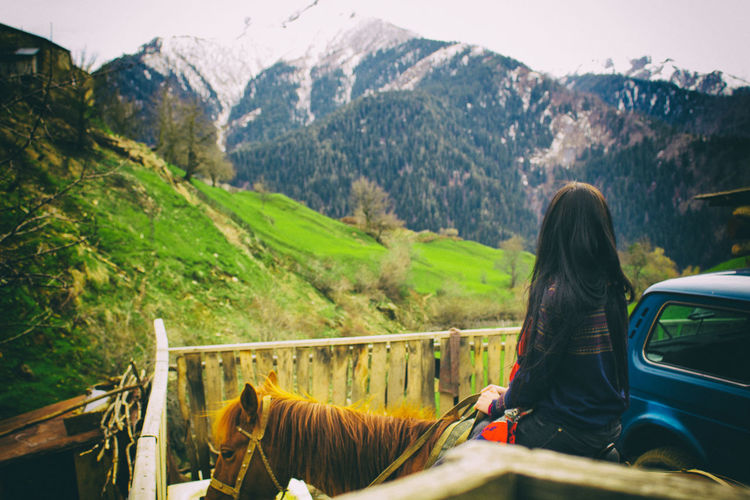 Woman riding horse by fence against mountains