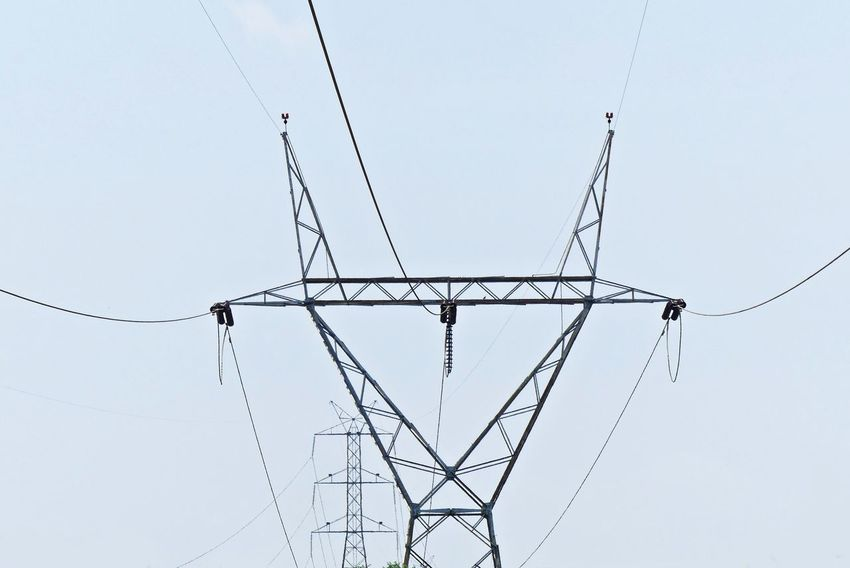 High-Voltage Power Transmission Tower in Clear Sky Background Power Transmission Background Cable Day Electricity  Energy High-voltage Low Angle View No People Outdoors Power Supply Sky Technology Tower