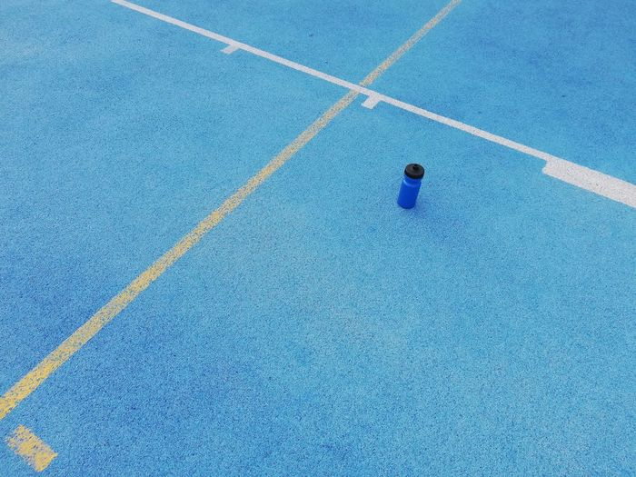 High angle view of blue water bottle running tracks