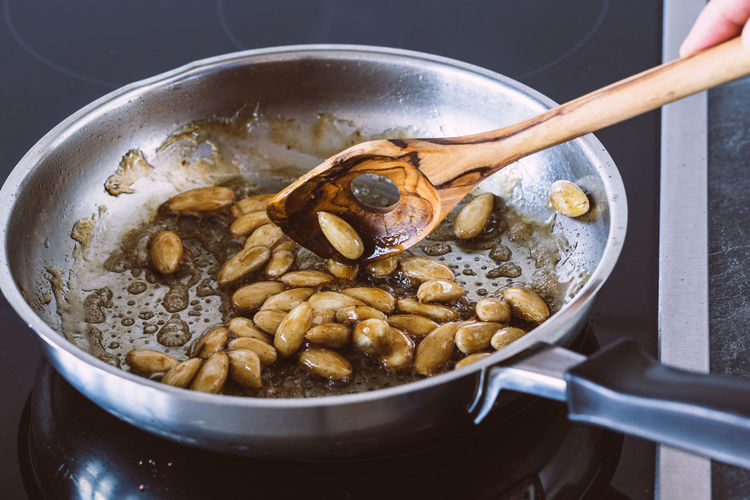 Cropped Image Of Hand Preparing Caramelized Almonds In Cooking Pan