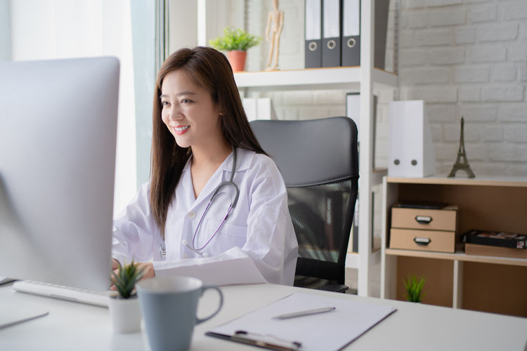 Doctor using computer while sitting on table