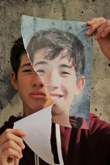 Portrait of a sad boy holding a torn portrait o happy boy