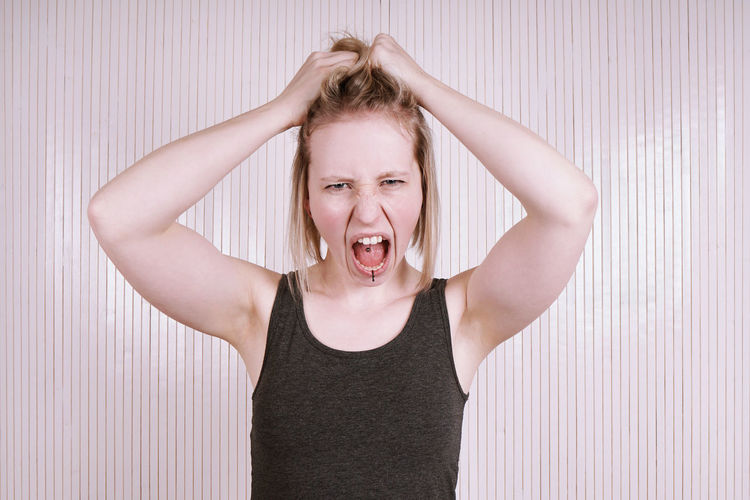 Angry Woman Adult Anger Blond Hair Front View Furious Fury Girl Hand In Hair Hysterical Indoors  Looking At Camera Mad One Person People Real People Scream Screaming Shouting Young Adult Young Women
