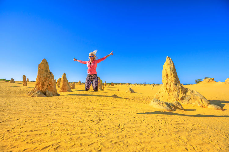 Woman with arms outstretched jumping against sky
