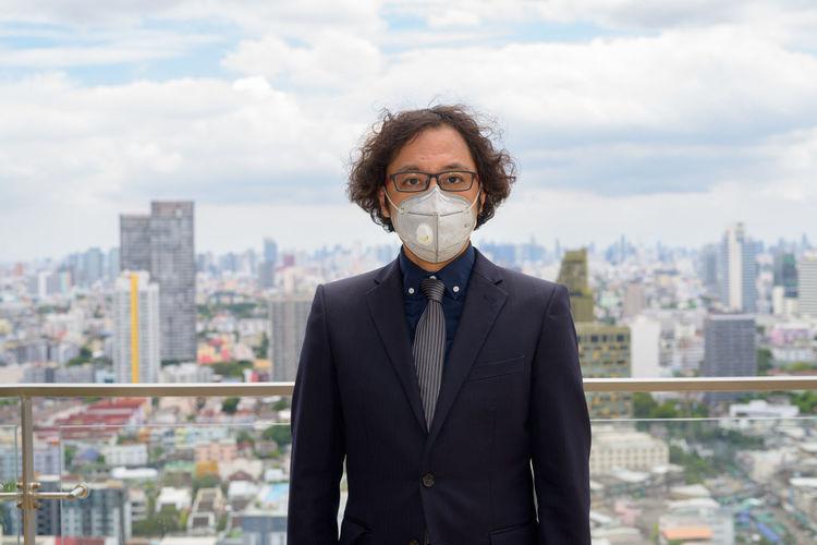 Portrait of man standing against buildings in city