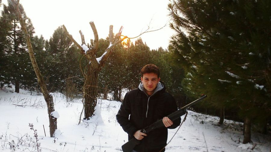 High Angle Portrait View Of Young Man With Shotgun In Forest