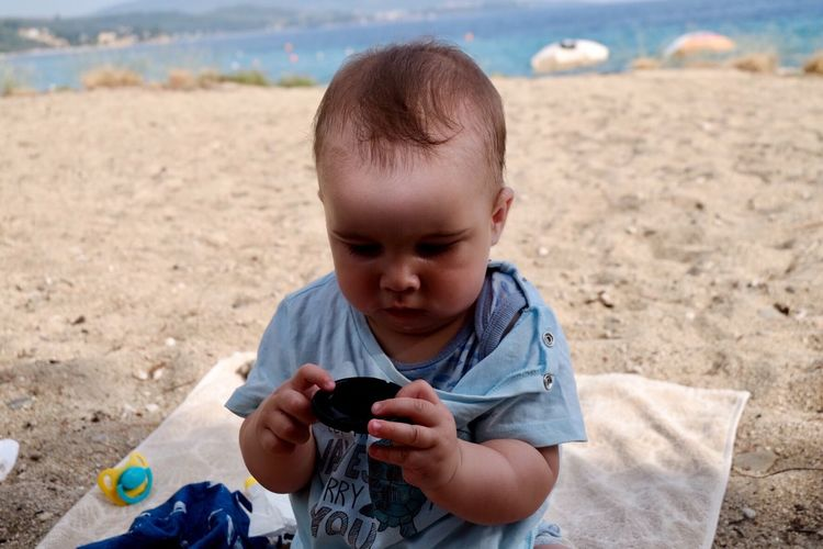 Cute boy playing with toy at beach