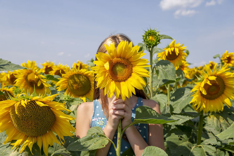 Girl holding sunflower in front of her face in the field. generation z.