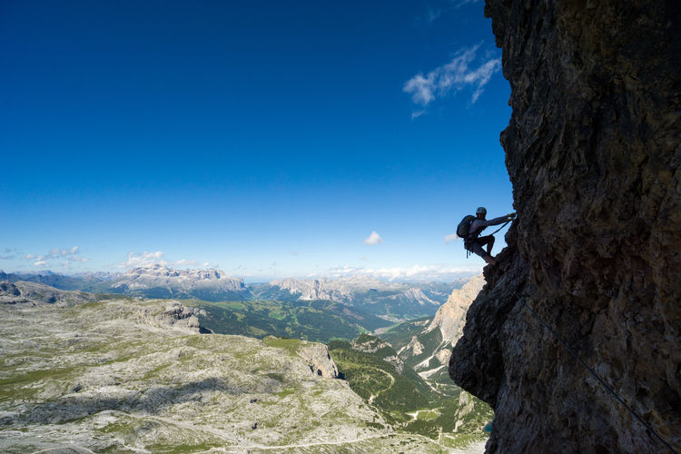 Side view of woman rock climbing against sky