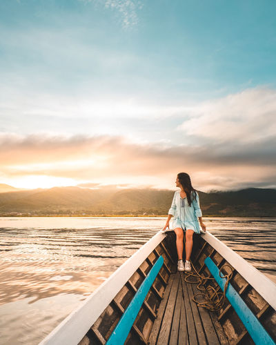 ASIA Beauty In Nature Boat Casual Clothing Cloud - Sky Full Length Girl Idyllic Inle Lake Leisure Activity Lifestyles Looking At View Myanmar Nature One Person Outdoors Real People Rear View Scenics - Nature Sky Standing Sunset Vacations Water Young Adult