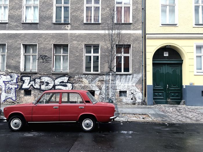 Red car parked outside building