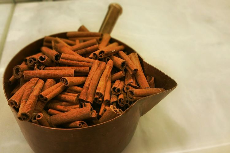 High angle view of cinnamon sticks in bowl on table