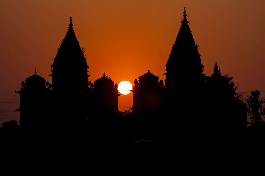 Silhouette of temple and cenotaphs at sunset by Betwa river, Orchha, India. Architecture Evening Incredible India India Monument Orchha Palace Silhouette Sun Sunset Temple Worship