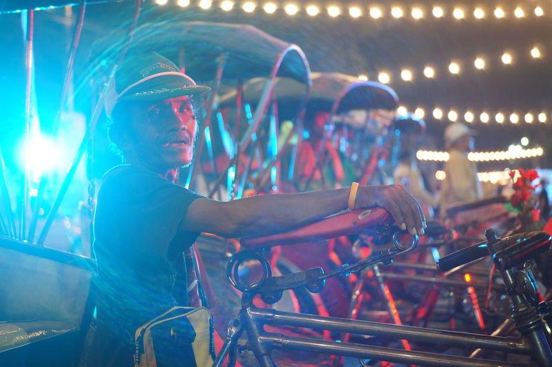 People on illuminated bicycle at night