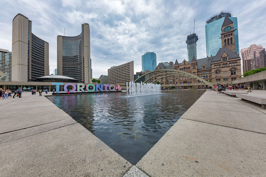 TORONTO, CANADA - JUNE 09, 2018: Beautiful wide view of the Nathan Phillips Square in the city City Hall Toronto Canada Architecture Building Building Exterior Built Structure City City Life Cityscape Cloud - Sky Day Financial District  Incidental People Modern Nathan Phillips Square Nature Office Office Building Exterior Outdoors Sky Skyscraper Tall - High Tower Urban Skyline Water