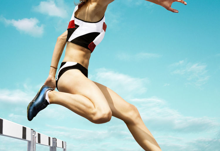 Low section of woman jumping over hurdle against blue sky