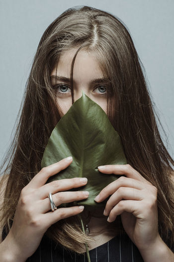 Blue Eyes Green Portrait Of A Woman Beautiful Woman Brown Hair Front View Hair Hairstyle Headshot Holding Indoors  Leaf Leisure Activity Lifestyles Long Hair Looking At Camera Obscured Face One Person Portrait Real People Studio Shot Teenager Women Young Adult Young Women The Portraitist - 2018 EyeEm Awards The Still Life Photographer - 2018 EyeEm Awards My Best Photo