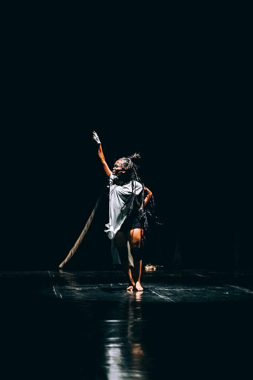 FULL LENGTH OF WOMAN DANCING AGAINST BLACK SKY