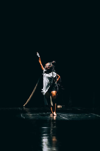Full length of woman dancing against black background at night