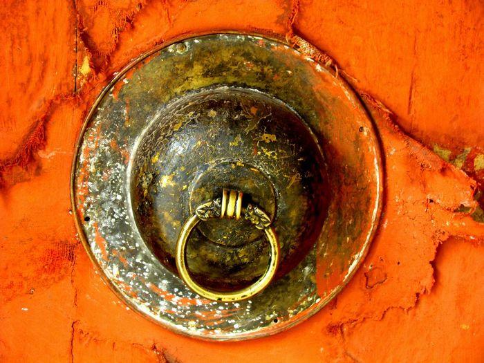 Close-up of metal hook on orange wall