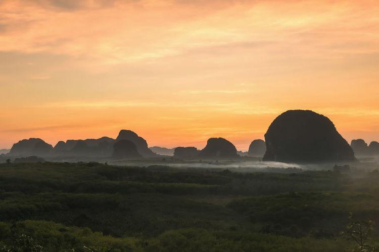 Silhouette rocks on landscape against sky during sunset