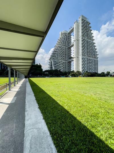 Footpath by buildings against sky in city